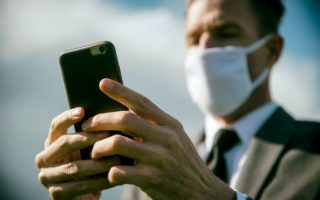 A man in a mask holds a phone