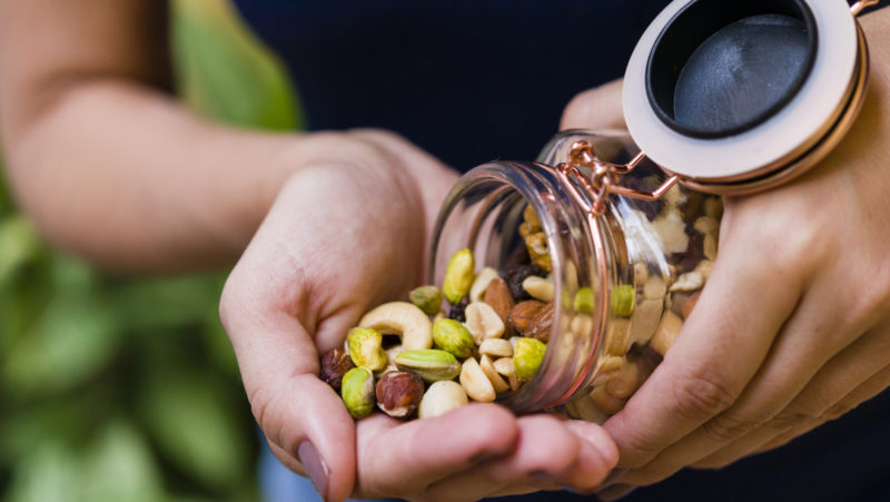 A person pours a handful of nuts from a jar