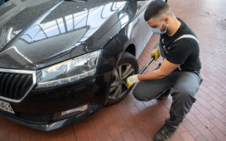 A mechanic in a mask changes a car tyre