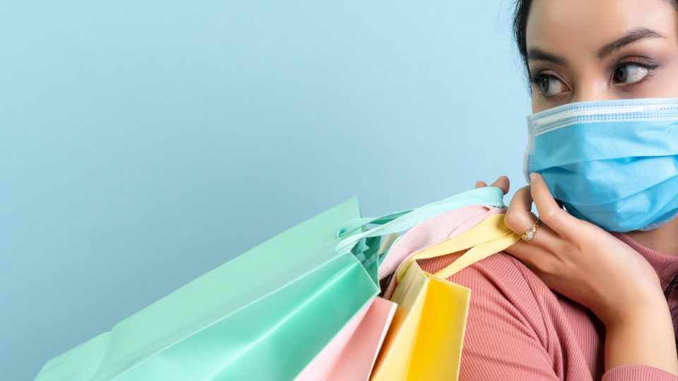 A woman wearing a mask holding shopping bags