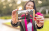 Young woman taking a selfie in a park in autumn