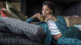 Woman wearing sports clothes whilst drinking tea in front of a warm fireplace