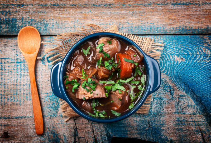 Meat stew with vegetables and herbs on old wooden table - stock photo