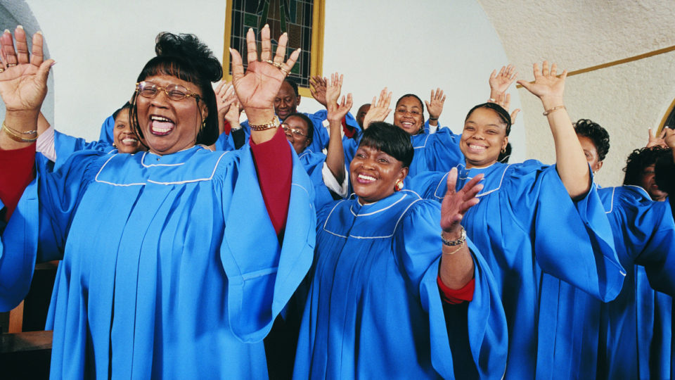 Twelve Gospel Singers With Raised Hands Singing in a Church Service - stock