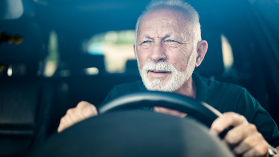 Senior man having bad eye sight and making effort to see the road.
