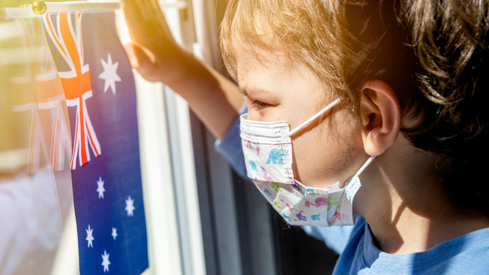 Little child looking through a window using a surgical mask holding an Australian flag