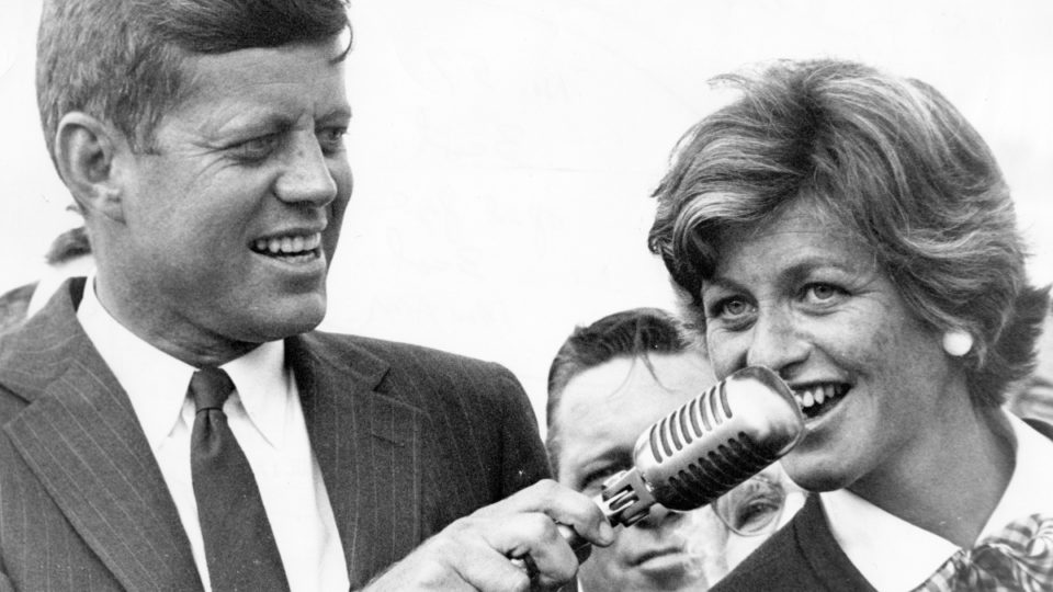 Sen. John F. Kennedy (left) and Jean Kennedy Smith (right) speak to a large crowd of people at Logan Airport in Boston on July 17, 1960. The crowd welcomed him home and cheered him on after he became the Democratic nominee for President of the United States.