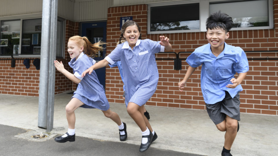 Three children running out from school across playground laughing