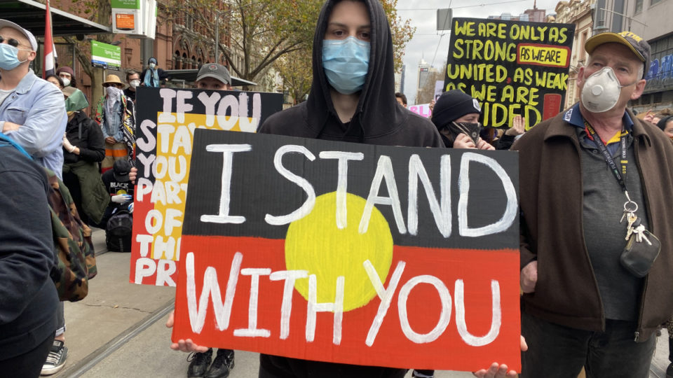 A Black Lives Matter protestor holds a sign with the Aboriginal flag and the words 'I stand with you'.