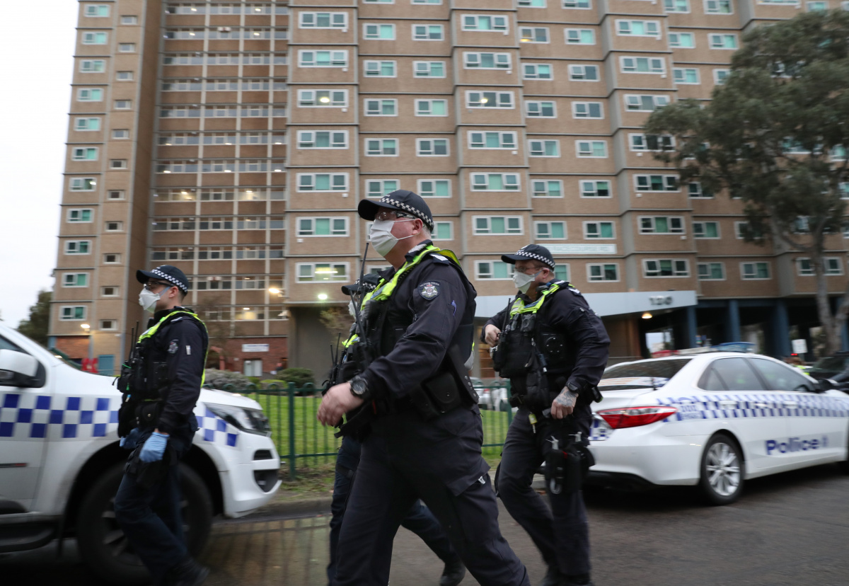 Police are seen enforcing a lockdown at public housing towers on Racecourse Road in Flemington, Melbourne.
