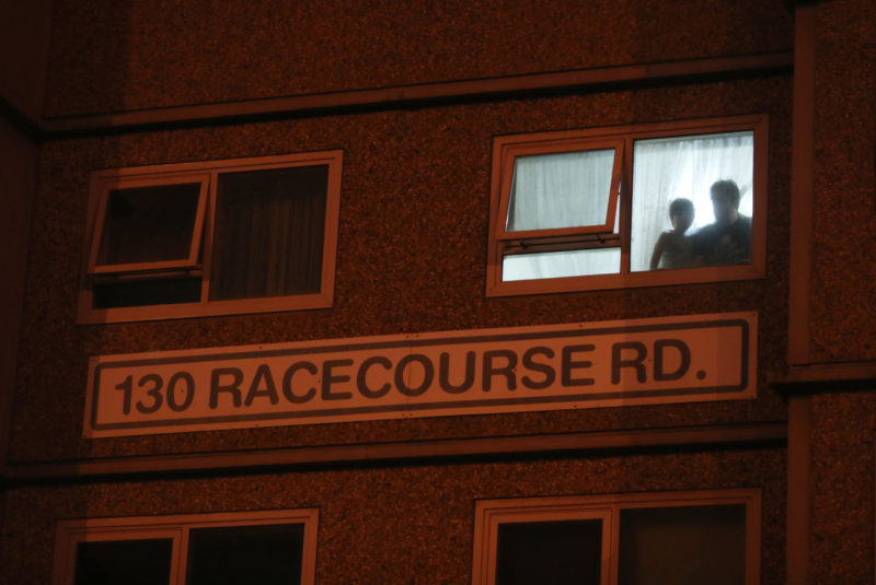 Residents watch from their window as police enforce a lockdown at public housing towers in Melbourne.