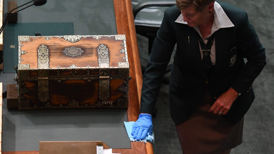 A parliamentary attendant disinfects alongside the dispatch box following Question Time in the House of Representatives at Parliament House