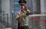 A Chinese paramilitary police officer gestures and speaks over his two-way radio whlie standing at the entrance gate of the Australian embassy in Beijing