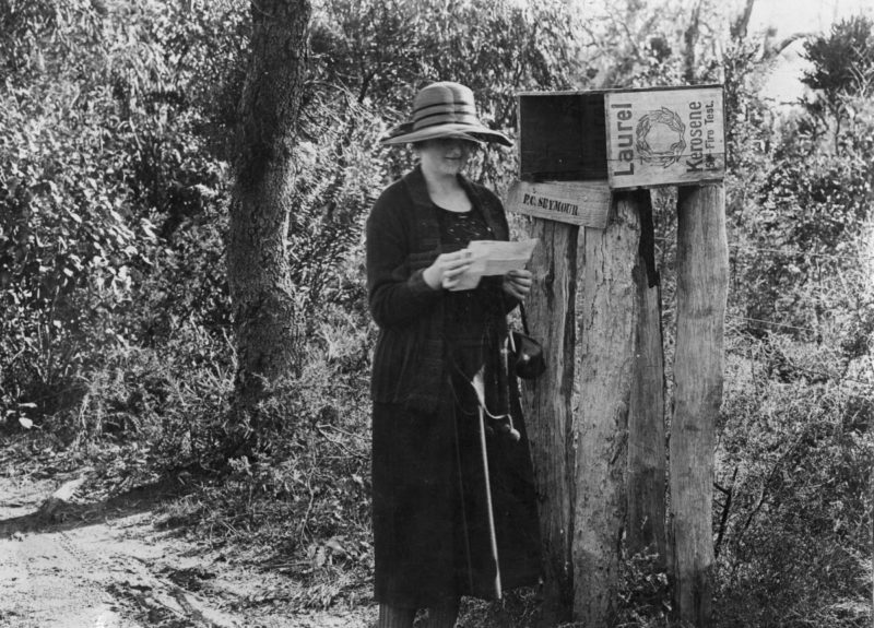 circa 1910: A woman picking up her mail from a roadside post box in rural New South Wales, Australia. (Photo by Hulton Archive/Getty Images)