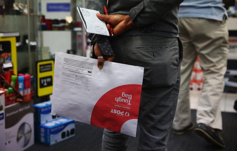 People wait in line inside Darlinghurst post office