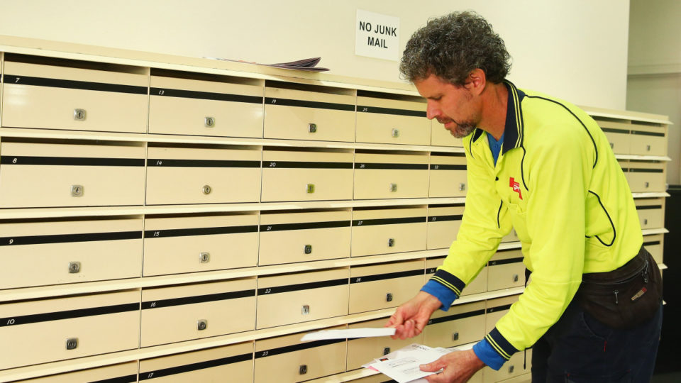A postman delivers mail to a building in Surry Hills