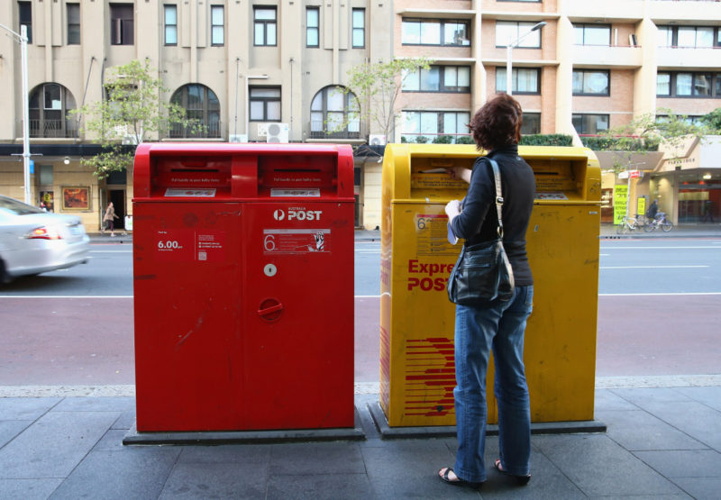 A woman posts mail via an Express Post box located on Oxford st outside the Darlinghurst Post Office