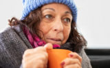 An elderly homeless woman with a cup of soup
