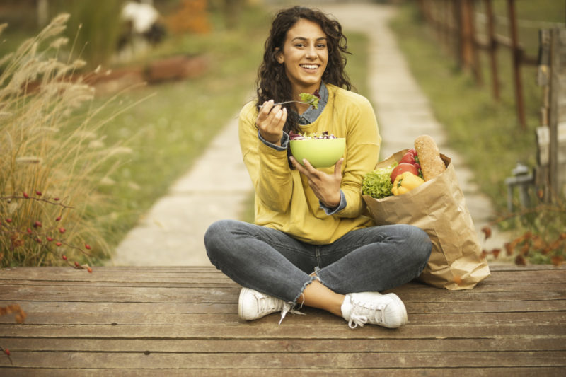 Happy young woman resting, eating fresh salad and sitting near paper bag full of groceries