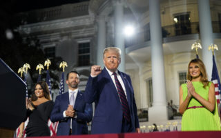 President Donald Trump is joined on stage by family members during the final night of the Republican National Convention, on the South Lawn of the White House in Washington, on Thursday, Aug. 27, 2020. From left: Kimberly Guilfoyle, Donald Trump Jr., President Trump and first lady Melania Trump. (Doug Mills/The New York Times)