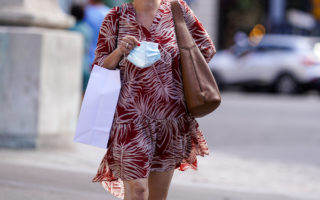 A passerby wears, a red and white floral print flowing dress, a brown leather Prada bag, holds a white paper shopping bag and a protective face mask, on July 11, 2020 in Paris, France.