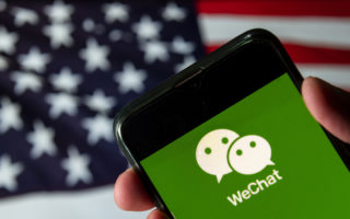 In this photo illustration the Chinese multi-purpose messaging social media and mobile payment app developed by Tencent, WeChat logo is seen on an Android mobile device with United States of America flag in the background.