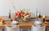 Mid Century Modern Beautiful Styled Pink and Wedding Flowers on Wooden Table with place setting and invite