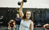 Smiling woman doing one arm overhead dumbbell press during class in gym