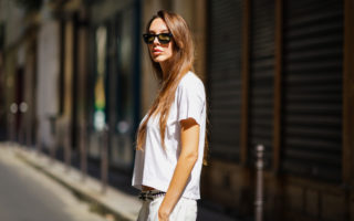 Estelle Chemouny wears sunglasses, a golden necklace, a white t-shirt, a black studded belt from Zadig & Voltaire, white pants, on August 26, 2020 in Paris, France