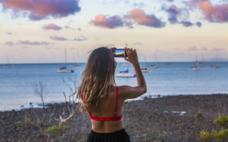 A girl takes a photo of the sunset over Airlie Beach Harbor