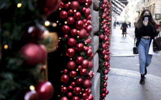 A woman walks past christmas decorations in a shopping street in the centre of Rome on November 26, 2020 in Rome, Italy