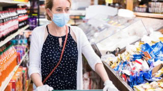 Woman pushes a shopping cart in a supermarket during the coronavirus pandemic. She is wearing a protective face covering as well as protective gloves