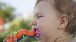 baby eating plastic toy
