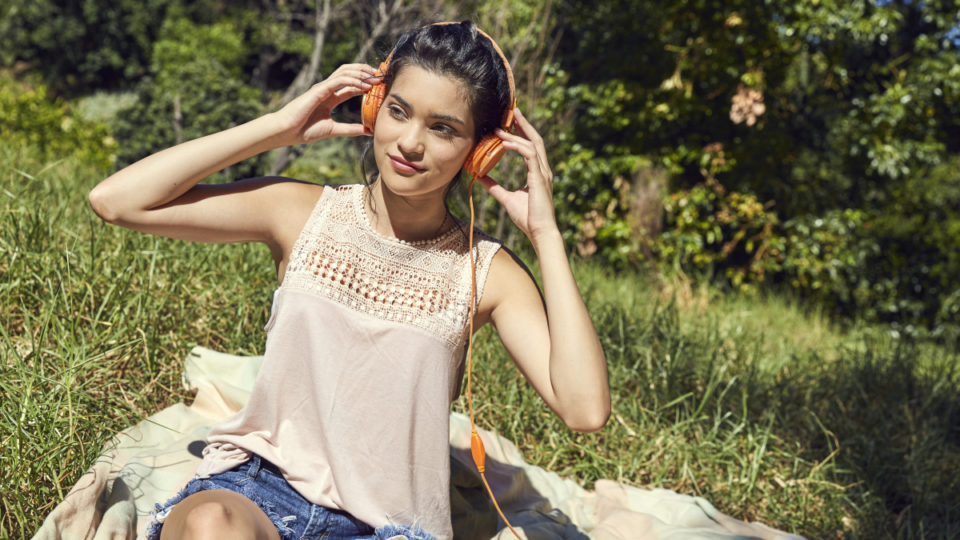Portrait of young woman sitting on blanket listening music with headphones