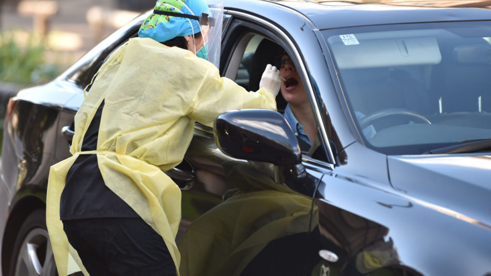 A medic takes a nasal swab from a driver at a drive-through testing centre for the COVID-19 coronavirus in Sydney