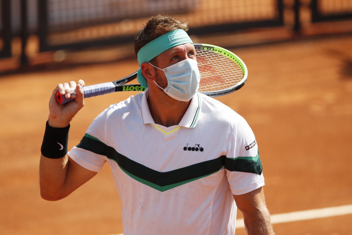Tennys Sandgren of the United States wears a face mask on court.