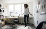 Businesswoman in office, training with skipping rope