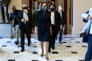 Speaker of the House Nancy Pelosi (D-CA) (C) wears a protective mask while walking to the House Floor at the U.S. Capitol on January 13, 2021 in Washington, DC.