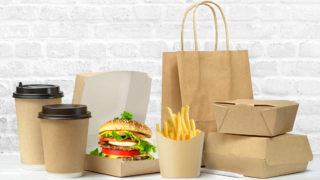 Fast food big lunch set of tasty hamburger, french fries, paper coffee cups, brown paper bag and box on the table on white brick wall background