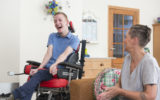 Color image of a real life young physically impaired ALS patient spending time with his mother at home