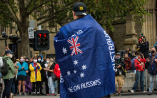 A man wearing a 'Proud Boys' shirt and an Australian flag attends the Invasion Day rally in the city on January 26, 2021 in Melbourne, Australia.