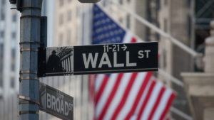 sign for Wall Street and American flags in New York, U.S