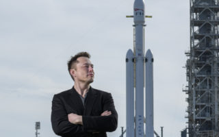 Elon Musk poses with the SpaceX Falcon Heavy rocket, NASA's Kennedy Space Center in Cape Canaveral, Fla., Feb. 5, 2018. By inserting himself into the confounding GameStop stock market drama, Musk has solidified his role as the ultimate insider outsider.