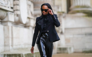 Emilie Joseph wears sunglasses from Gentle Monster, a lavalliere from Zara, a black shirt from Zara, a black blazer jacket from Balmain, black shiny vinyl leggings / pants, on January 29, 2021 in Paris, France.