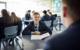 Point of view angle of teenage boy having a discussion during class.
