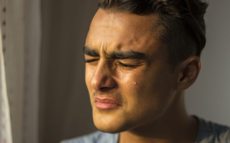 Portrait of crying young man closing his eyes