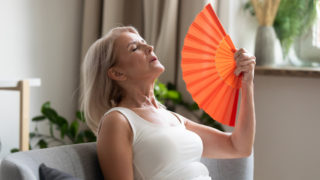 Stressed annoyed senior woman using waving fan suffer from overheating
