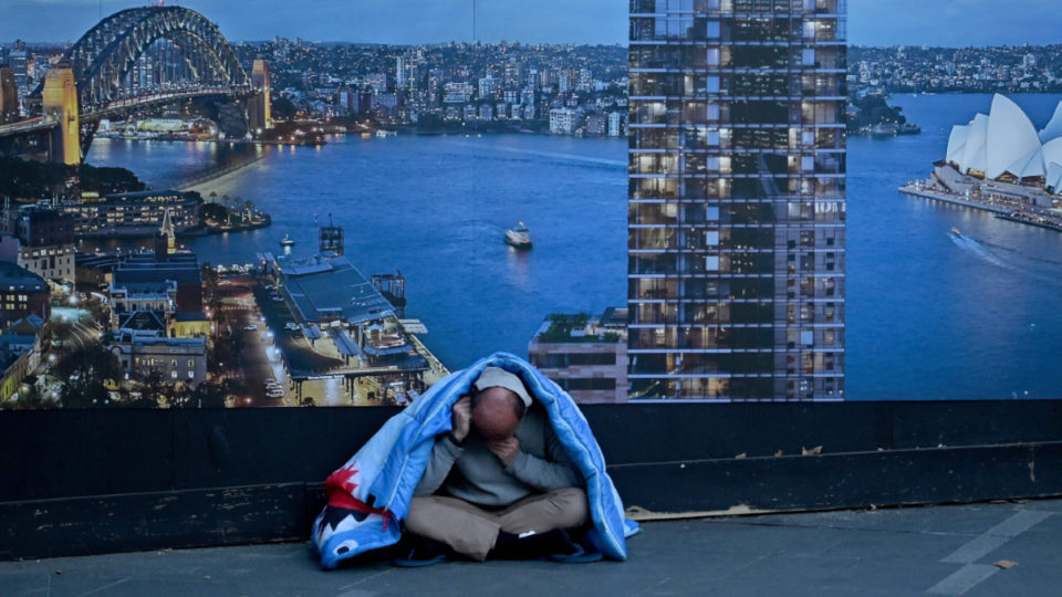 A homeless man sits in front of a billboard by a construction site in Sydney on July 24, 2019