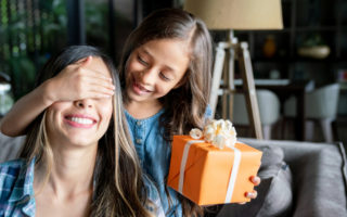 Cute little girl surprising her mom with a gift box for mother's day while covering her eyes