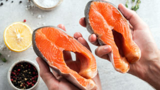Hands holding raw salmon steaks